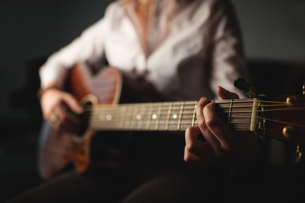 Frau, die eine gitarre in der musikschule spielt