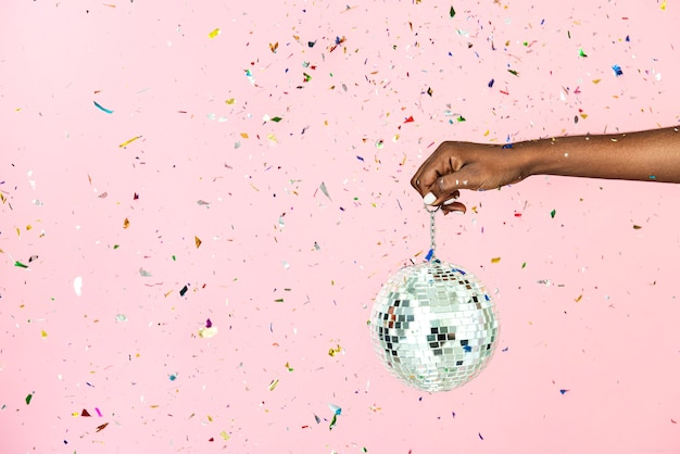 Frau, die eine glänzende silberne discokugel in einem konfetti hält