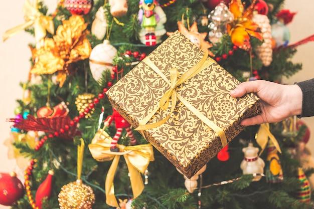 Frau, die eine große geschenkbox gegen erstaunlichen weihnachtsbaum hält.