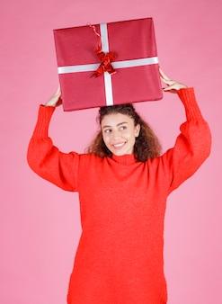 Frau, die eine große geschenkbox über dem kopf hält.