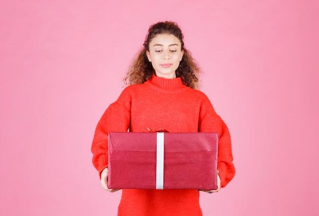 Frau, die eine große rote geschenkbox hält.