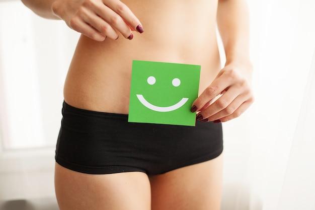 Frau, die eine grüne karte mit einem glücklichen lächeln in ihren händen hält