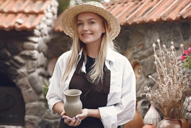Frau, die eine handgemachte vase hält