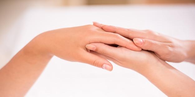 Frau, die eine handmassage am gesundheitsbadekurort empfängt.