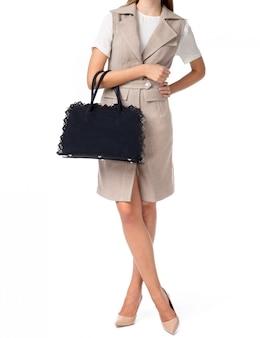 Frau, die eine handtasche lokalisiert auf weißem hintergrund hält