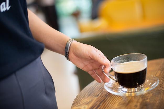 Frau, die eine heiße schwarze kaffeetasse auf dem tisch hält