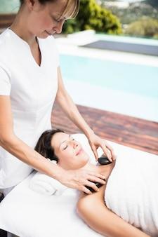 Frau, die eine heiße steinmassage vom masseur in einem badekurort empfängt