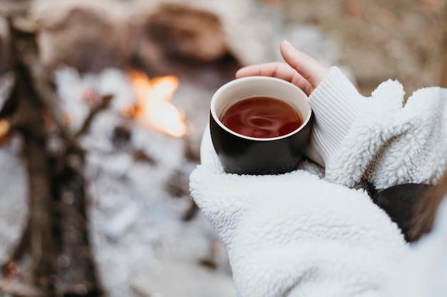 Frau, die eine heiße tasse tee draußen hält