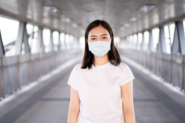 Frau, die eine hygieneschutzmaske trägt, um covid19-virus, covid-19 und pm2.5 zu schützen, während sie im überfüllten ort reisen. frau verwenden gesichtsmaske, um coronavirus-krankheit zu schützen. 2019-ncov-krise.
