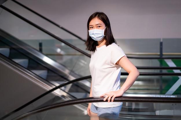 Frau, die eine hygieneschutzmaske trägt, um covid19-virus und pm2.5 verschmutzung während des reisens im überfüllten ort zu schützen.