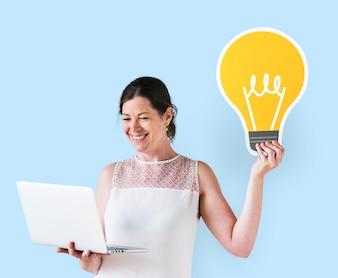Frau, die eine Ideenikone hält und einen Laptop verwendet