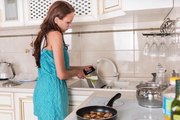 Frau, die eine käsereibe unter fließendem wasser in der küchenspüle wäscht, nachdem sie cheddar-käse für das rezept, das sie zubereitet, gerieben hat