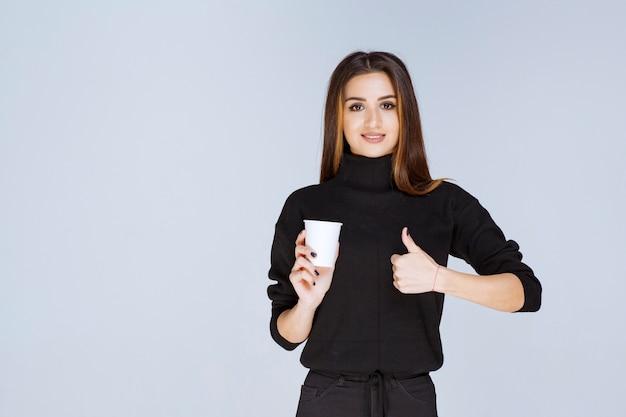 Frau, die eine kaffeetasse hält und den geschmack genießt.