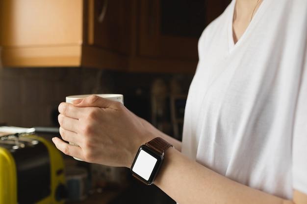 Frau, die eine kaffeetasse in der küche hält