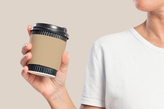 Frau, die eine kaffeetasse mit ärmeldesignraum hält holding