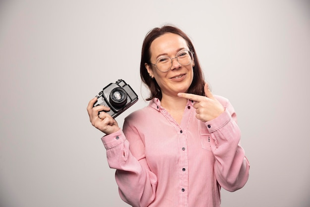 Frau, die eine kamera auf einem weiß zeigt. foto in hoher qualität