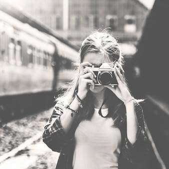 Frau, die eine kamera benutzt, die ein foto am bahnhof in graustufen macht