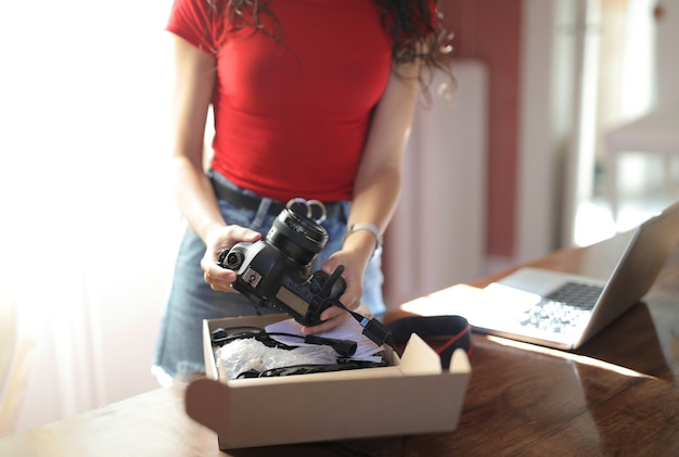Frau, die eine kamera mit einem notizbuch auf dem tisch hält