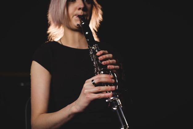 Frau, die eine klarinette in der musikschule spielt