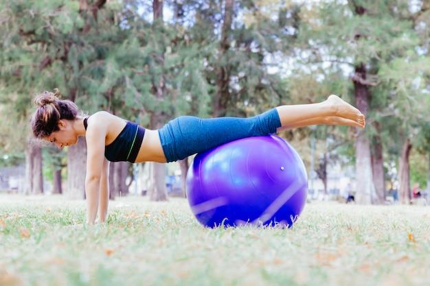 Frau, die eine kobra yoga pose über einem großen ball im freien tut. pilates gesunder lebensstil für menschen in yoga-übungen. training im freien und fit bleiben konzept. menschen, die wohlfühlmeditation im park machen.