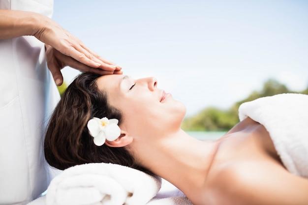 Frau, die eine kopfmassage vom masseur in einem badekurort empfängt