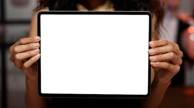 Frau, die eine leere bildschirmtafel an einer silvesterparty zeigt