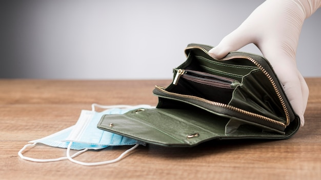 Frau, die eine leere brieftasche neben einer gesichtsmaske hält