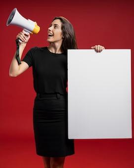 Frau, die eine leere fahne beim schreien in einem megaphon hält
