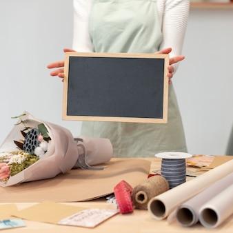 Frau, die eine leere kopienraumtafel hält