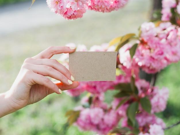 Frau, die eine leere visitenkarte auf natur im freien hält und zeigt