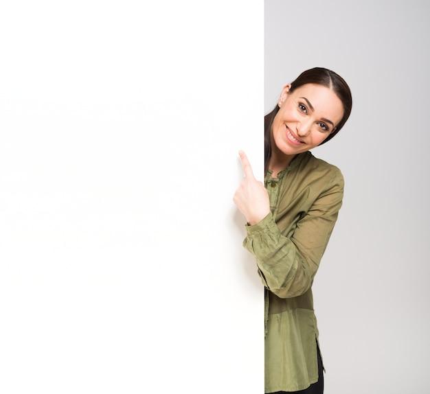 Frau, die eine leerplatte, einen raum für ihr text- oder produktbild zeigt