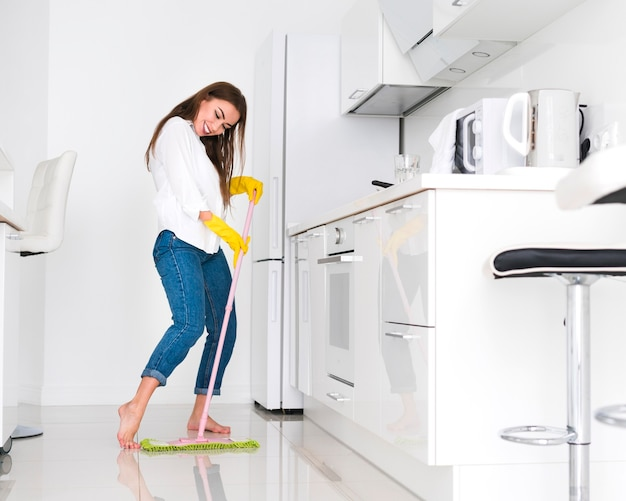 Frau, die eine lustige zeit beim putzen hat Premium Fotos
