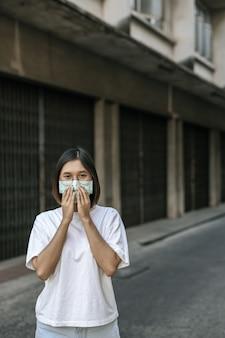 Frau, die eine maske auf der straße trägt.