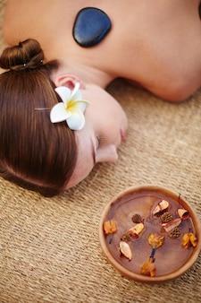 Frau, die eine massage mit heißen steinen genießen