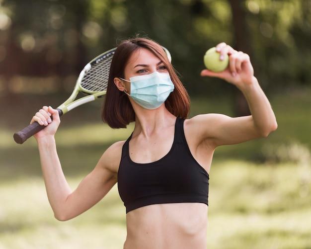Frau, die eine medizinische maske beim training für ein tennismatch trägt