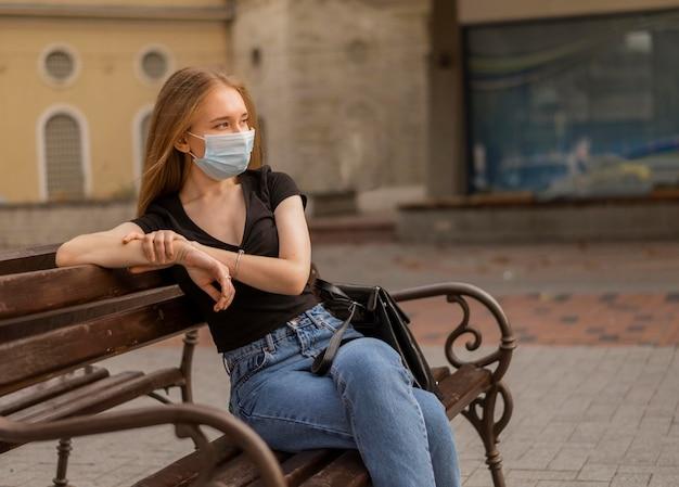 Frau, die eine medizinische maske draußen beim sitzen auf einer bank trägt