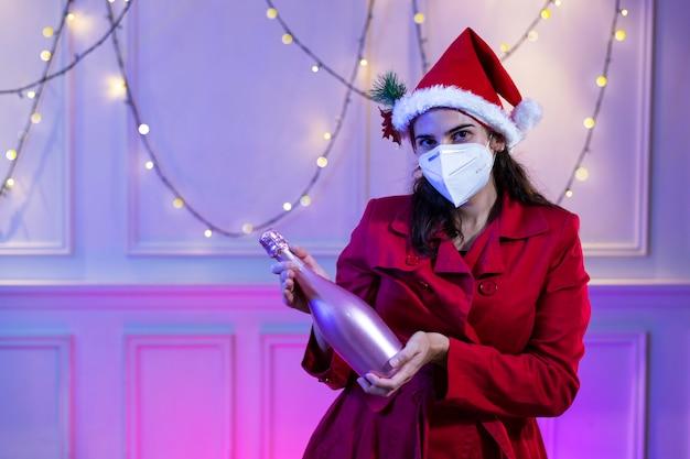 Frau, die eine medizinische maske kn95 und einen roten hut des weihnachtsmanns mit einem glücklichen ausdruck trägt, der allein weihnachten zu hause während covid 19 auf weißem weinlesehintergrund feiert