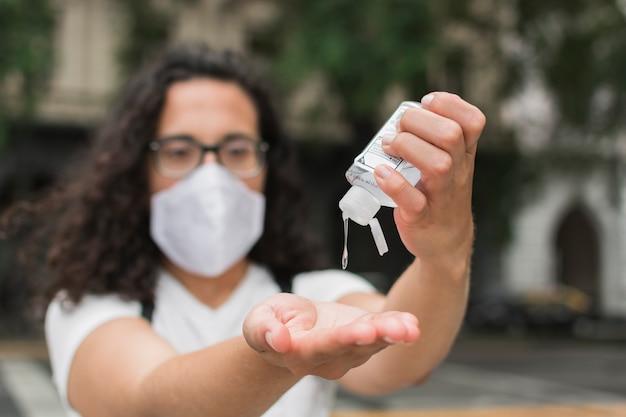 Frau, die eine medizinische maske mit händedesinfektionsmittel trägt