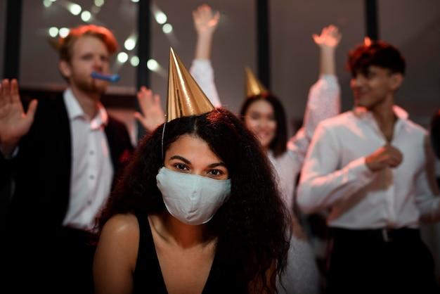 Frau, die eine medizinische maske neben ihren freunden auf silvesterparty trägt