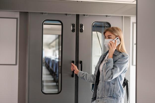 Frau, die eine medizinische maske trägt und telefoniert, während sie sich auf die reise mit dem zug vorbereitet