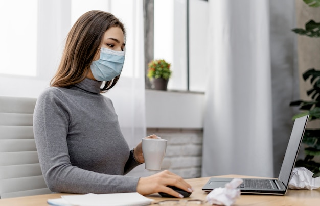 Frau, die eine medizinische maske trägt, während sie von zu hause aus arbeitet