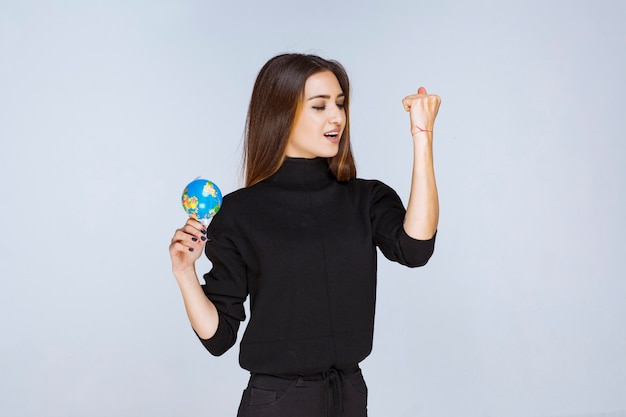 Frau, die eine minikugel hält und ihre faust zeigt.
