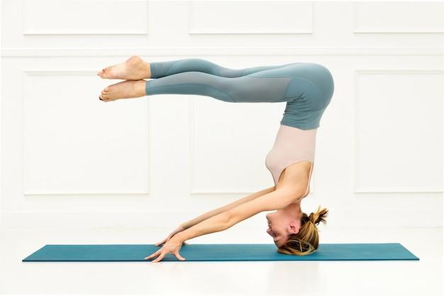 Frau, die eine mukta sirsasana variation yoga pose oder kopfstand der freien hände mit ausgestreckten beinen durchführt