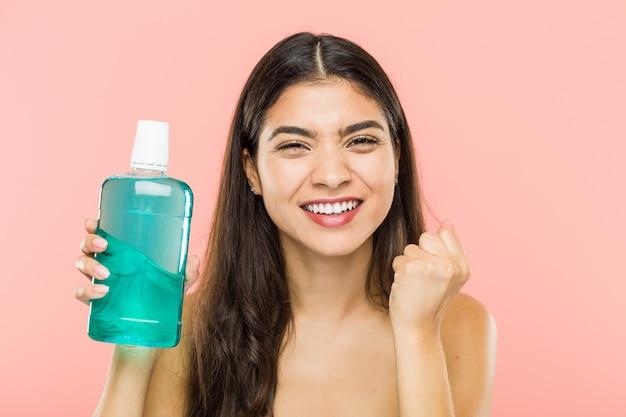 Frau, die eine mundwasserflasche hält