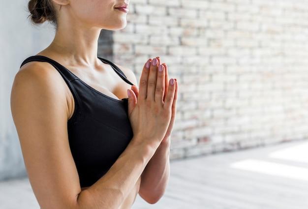 Frau, die eine namaste yogahaltung tut