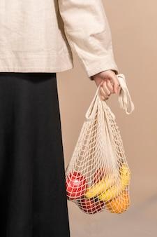 Frau, die eine netztasche benutzt, um früchte zu tragen
