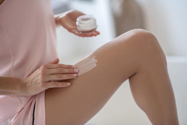 Frau, die eine neuartige creme auf ihr bein aufträgt