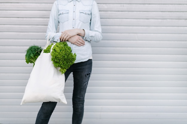 Frau, die eine öko-tasche mit lebensmittelgeschäft gefüllt hält. gemüse und obst hängen an einer tüte. ökologie- oder umweltschutzkonzept. weiße öko-tasche zum mock-up.