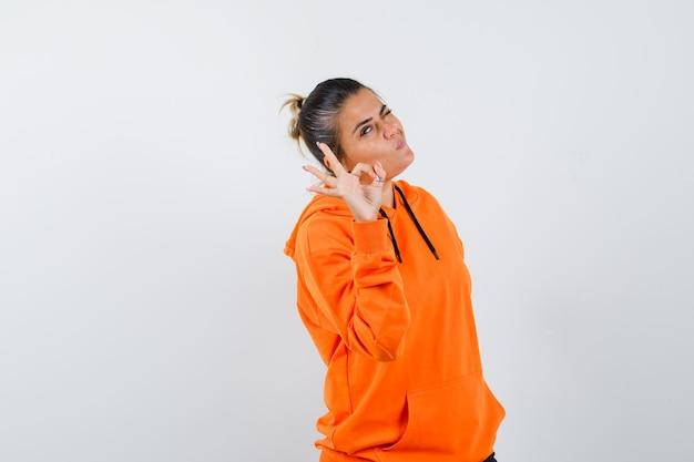 Frau, die eine ok geste in orangefarbenem hoodie zeigt und nachdenklich aussieht