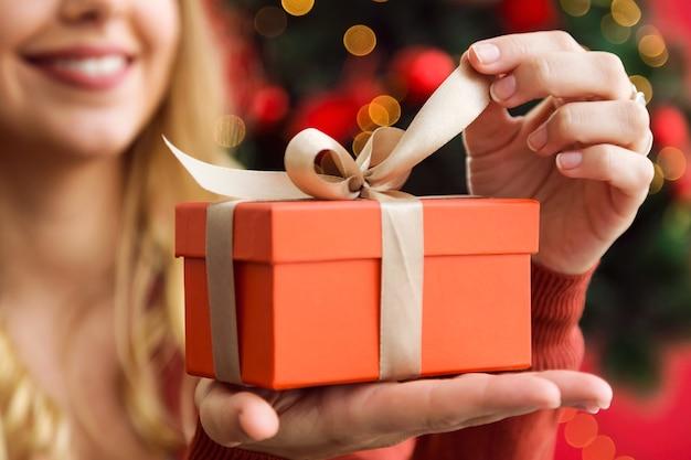 Frau, die eine orange geschenk öffnen